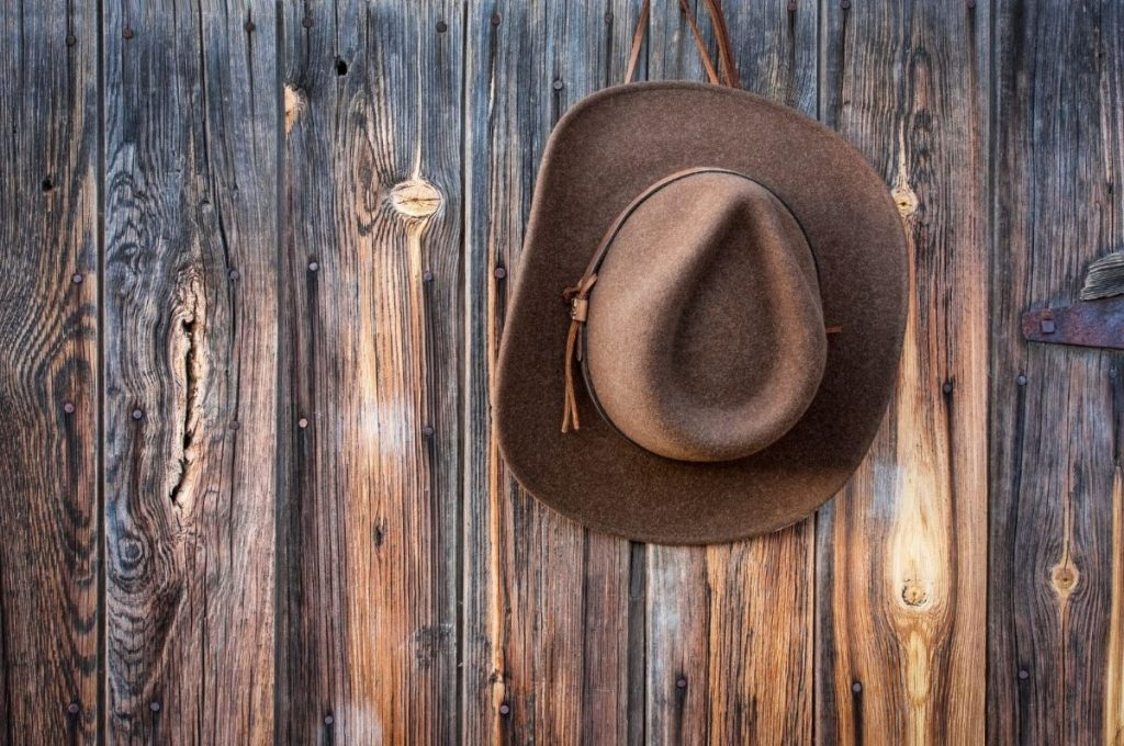 cowboy hat hanging from a wooden wall