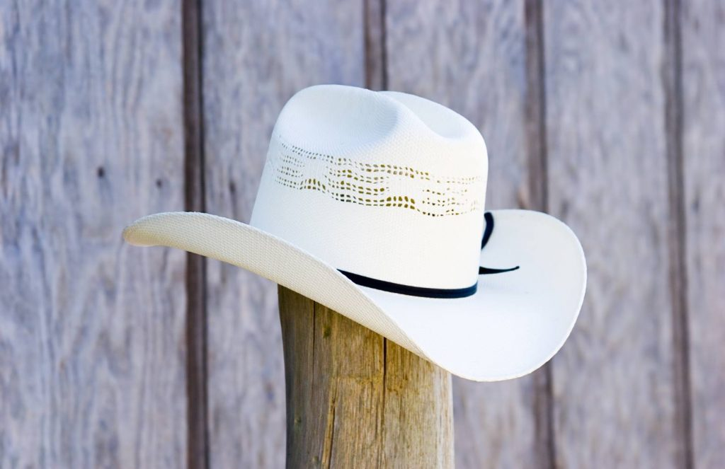 white cowboy hat on wooden post